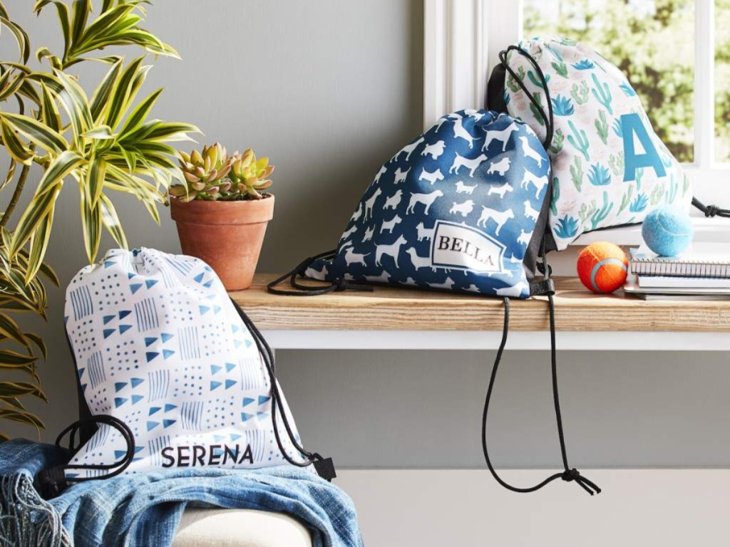 three shutterfly drawstring backpacks in home on windowsill