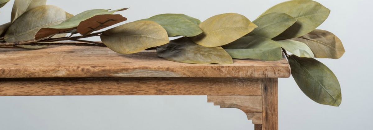 magnolia garland laying across wood shelf