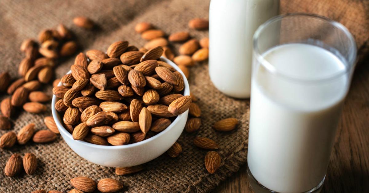 bowl of almonds on table next to almond milk