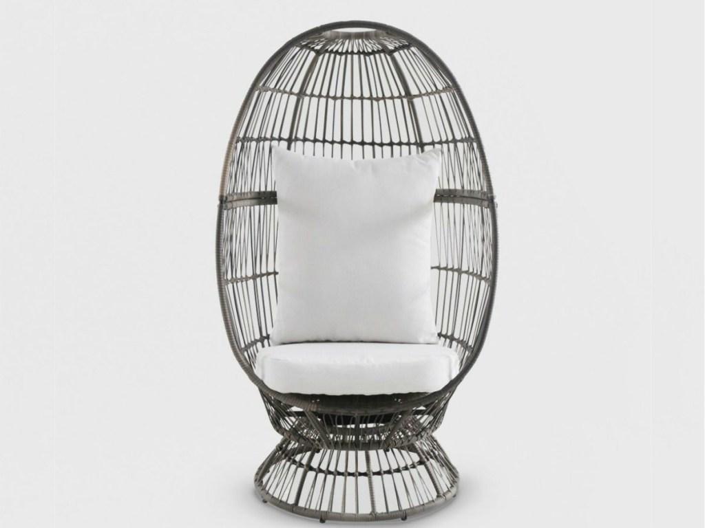 narrow egg chair with white pillows