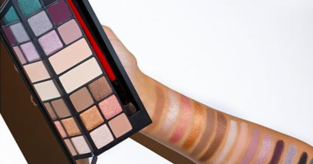Hand with eye shadow swatches on arm holding Smashbox The Love Edit: Romantic Eye Shadow Palette