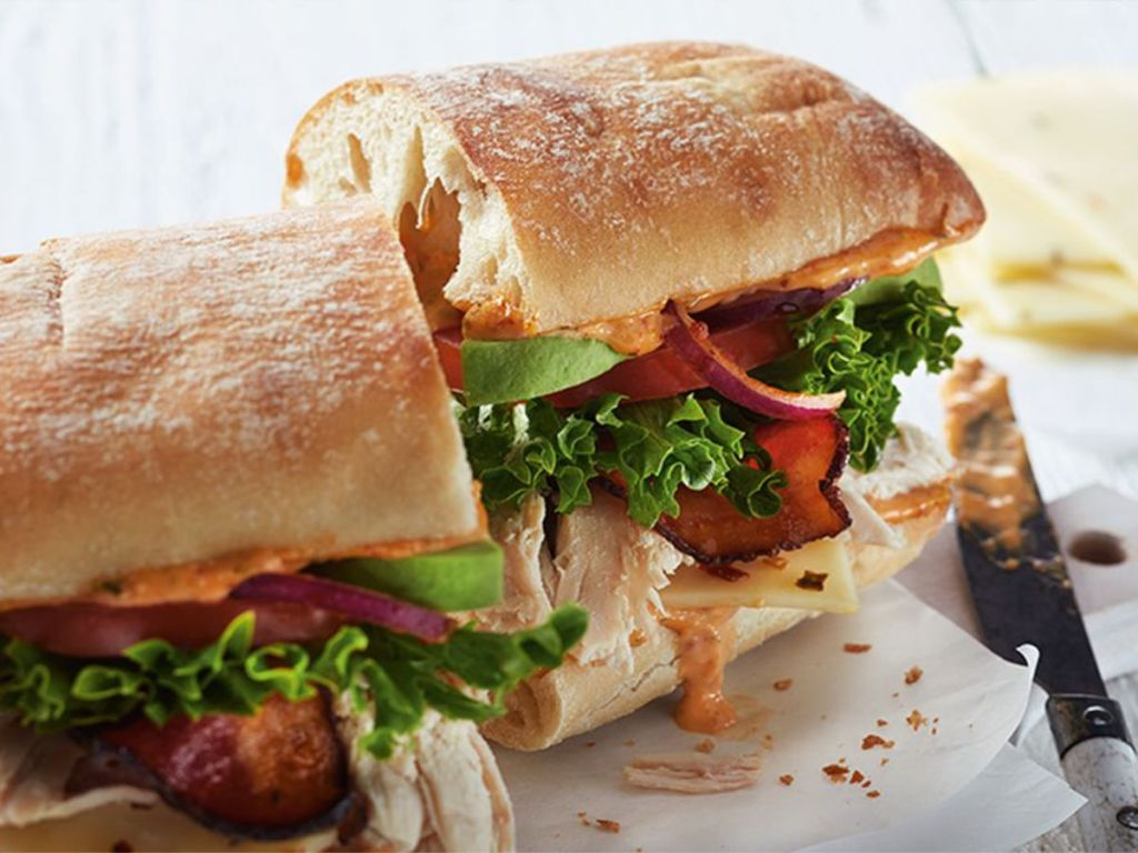 boston market Southwest Chicken BLT on ciabata with knife with chipotle aioli and cheese in background