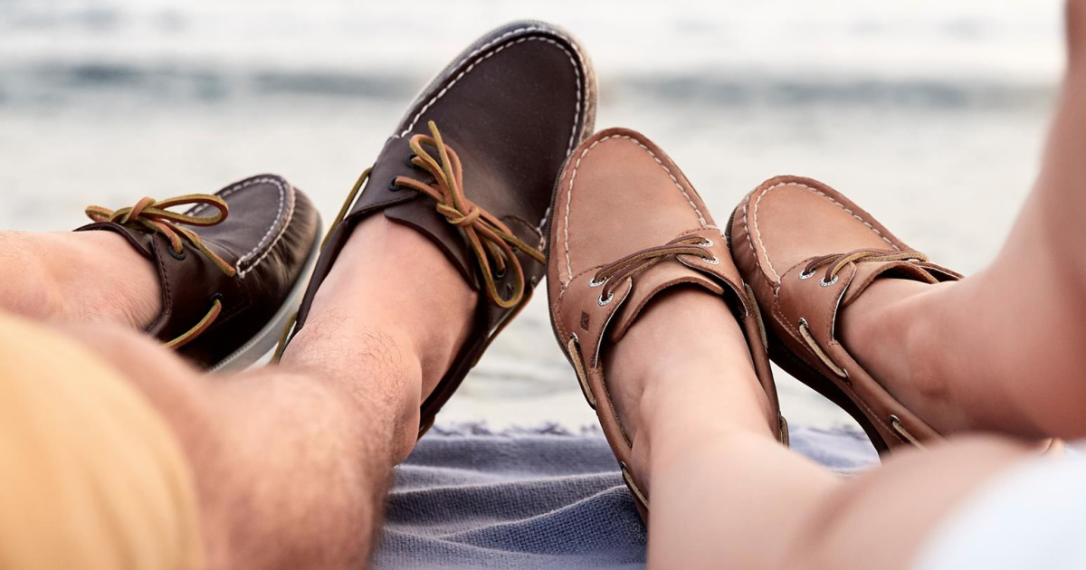men and women laying on a beach blanket wearing boat shoes