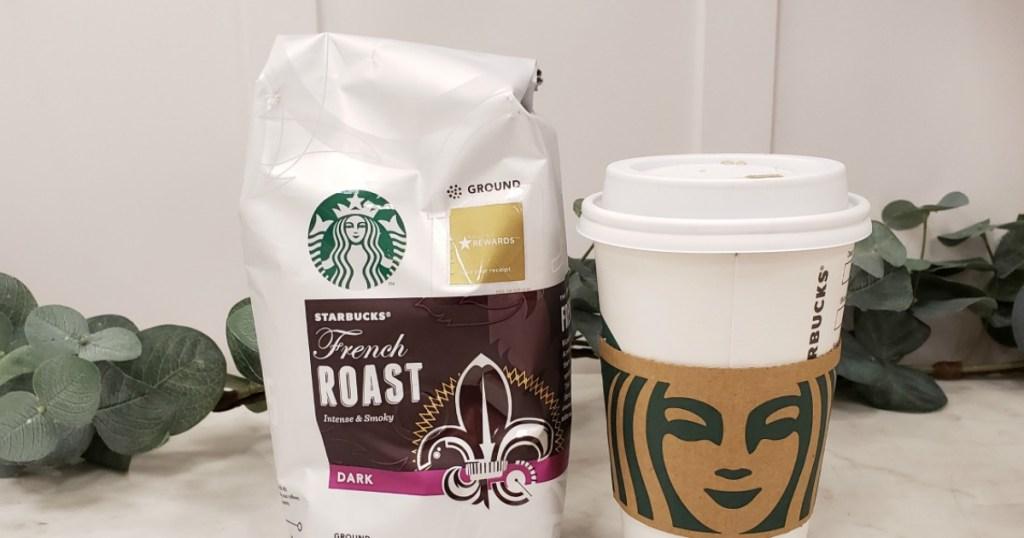 bag of Starbucks coffee next to Starbucks coffee cup