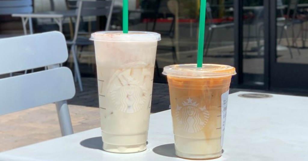 two iced Starbucks beverages sitting outside of Starbucks on a table