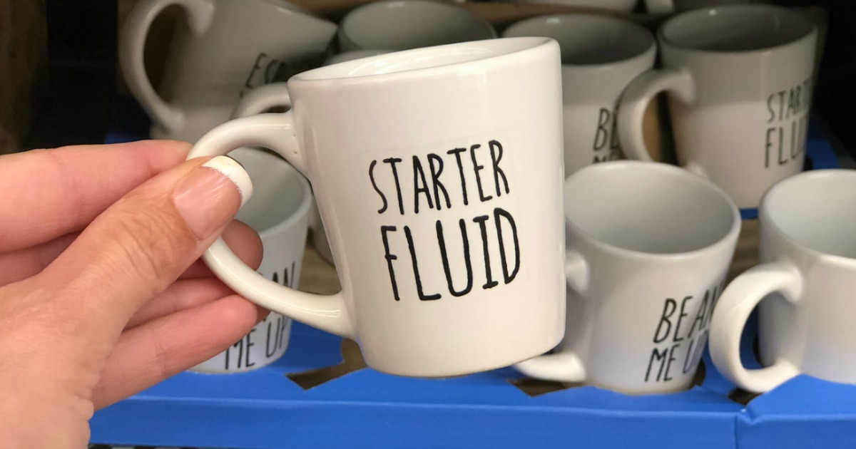 white espresso mugs with starter fluid written on it being held in a store