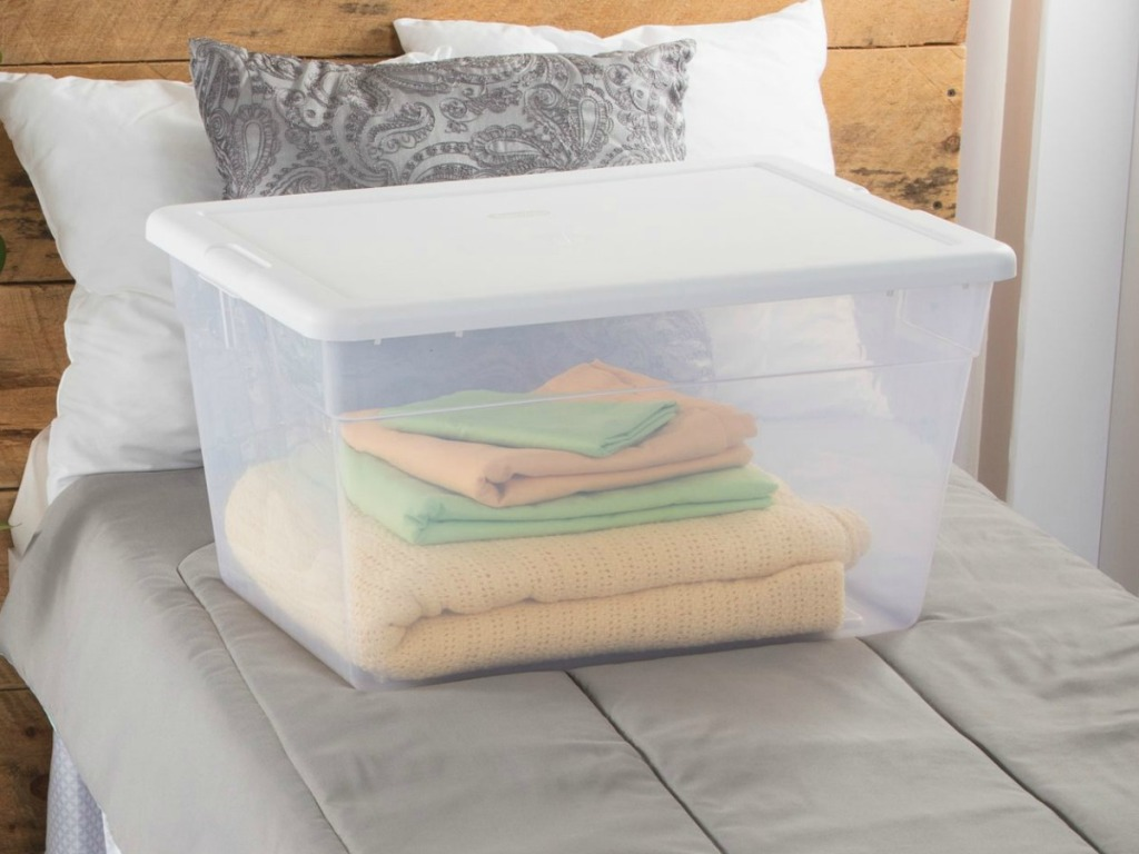 clear storage bin with white lid filled with bedding sitting on bed
