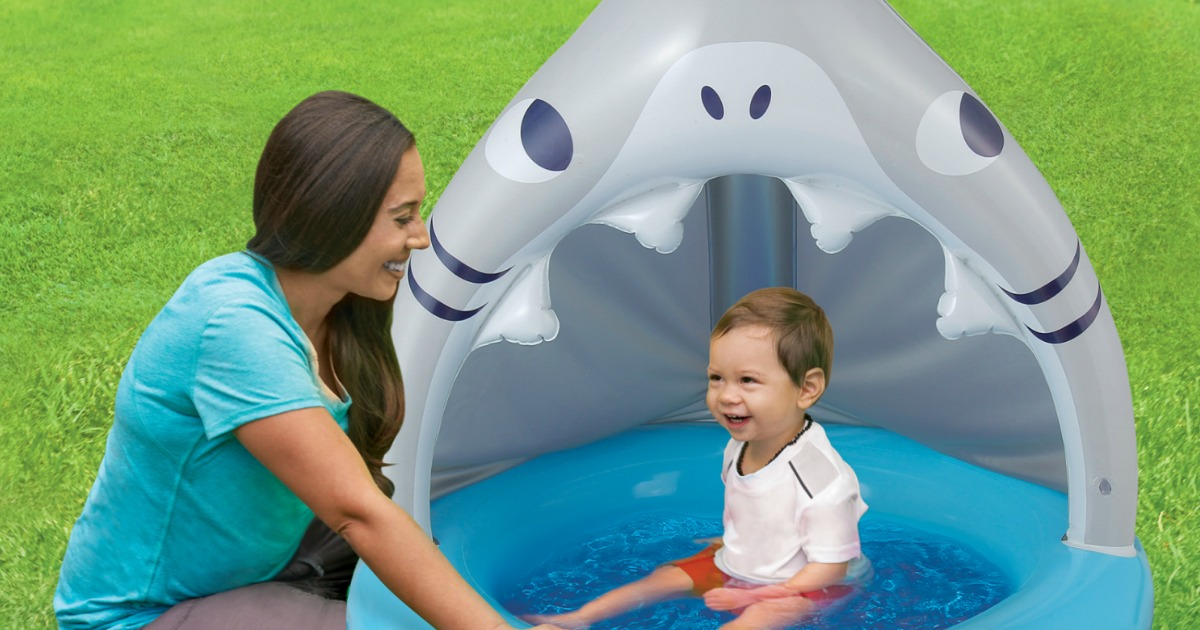 woman next to baby sitting in an inflatable shark-shaped pool