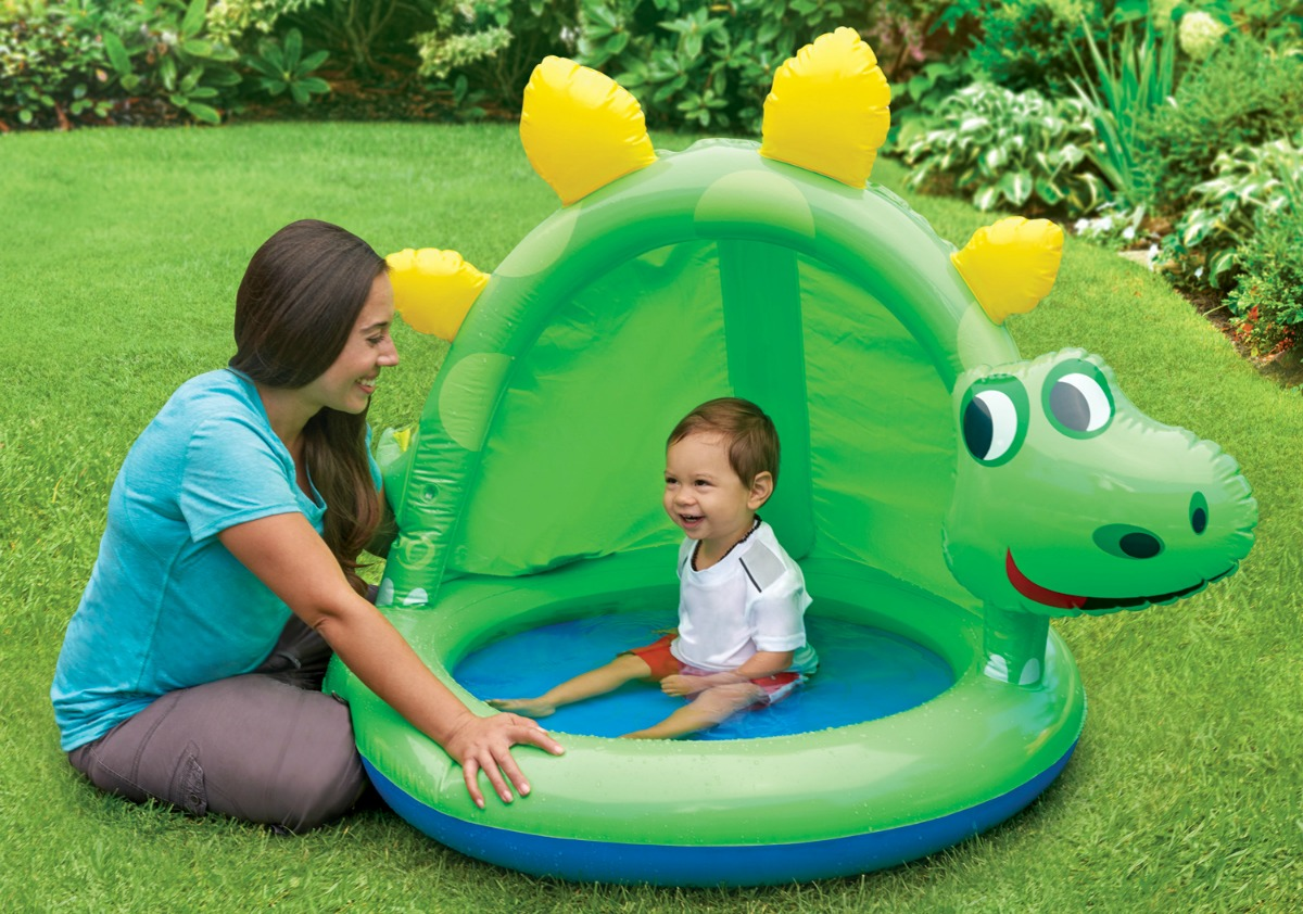 woman next to baby sitting in an inflatable dinosaur-shaped pool