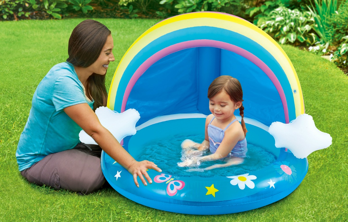 woman next to baby sitting in an inflatable rainbow-shaped pool