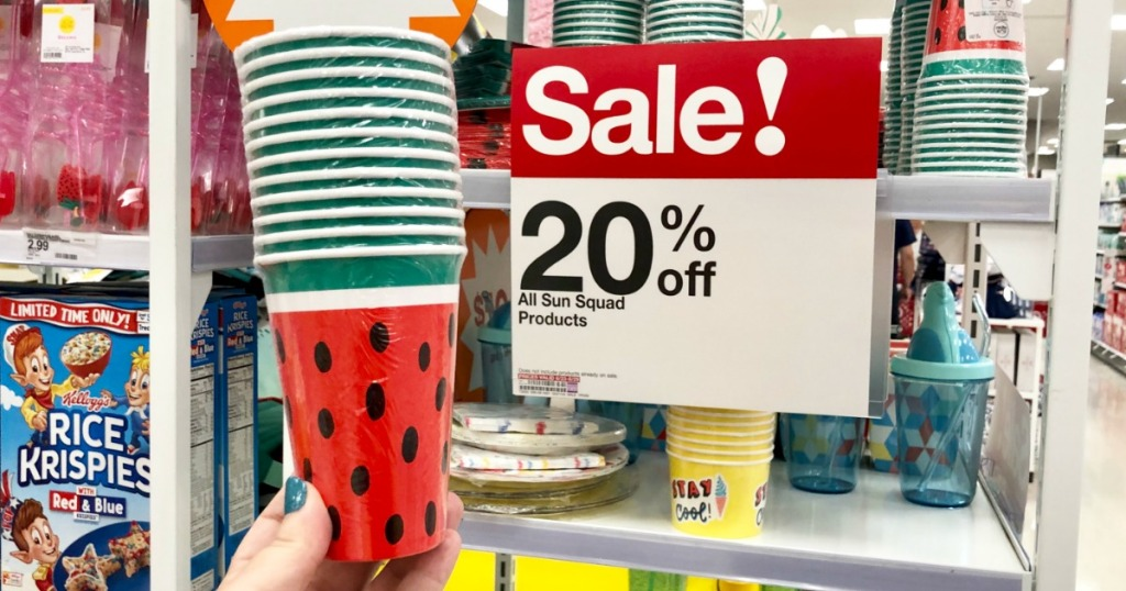 Sun Squad paper cups in watermelon print held up in front of a sale sign
