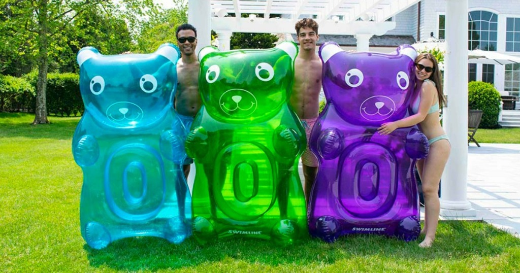 People holding Swimline Gummy Bear Pool Floats