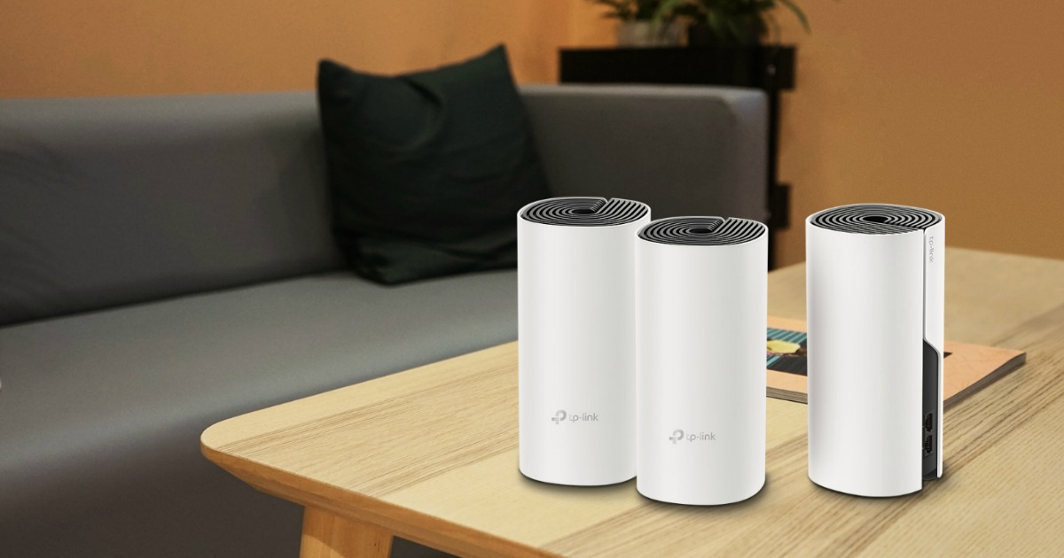 three sleek cylindrical wifi extenders on coffee table in front of modern gray couch