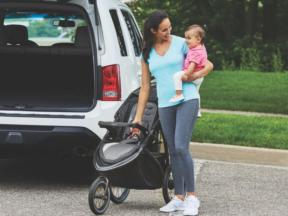 woman holding a baby standing next to a stroller and SUV
