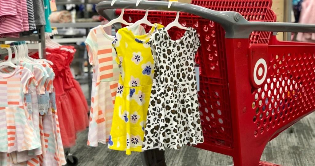 cute toddler girl dresses hanging on handle of Target cart