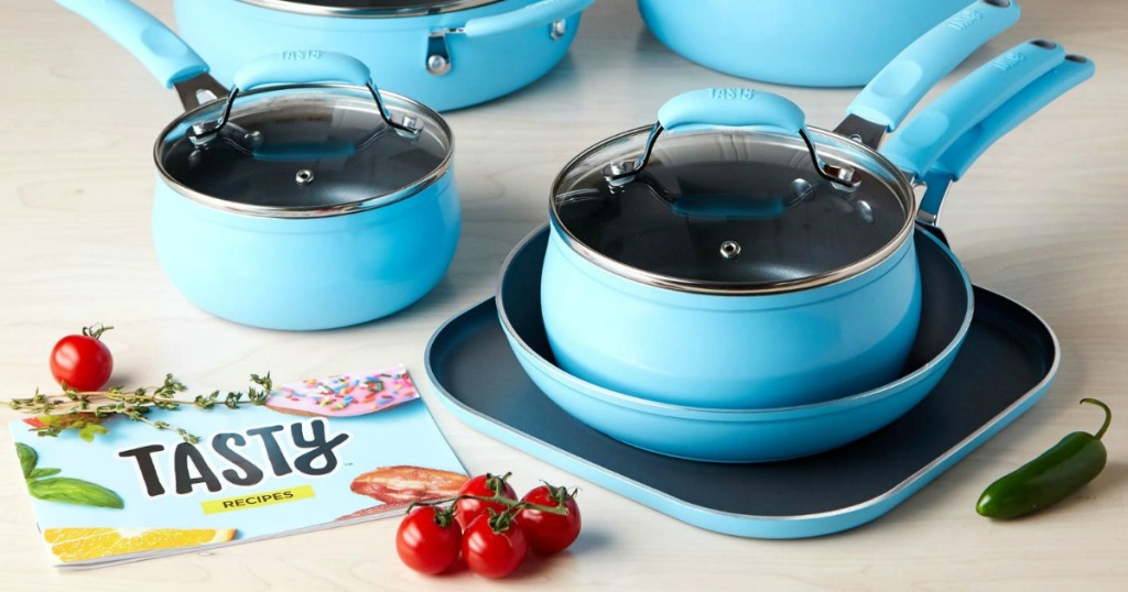 Tasty recipes booklet and blue cookware on table