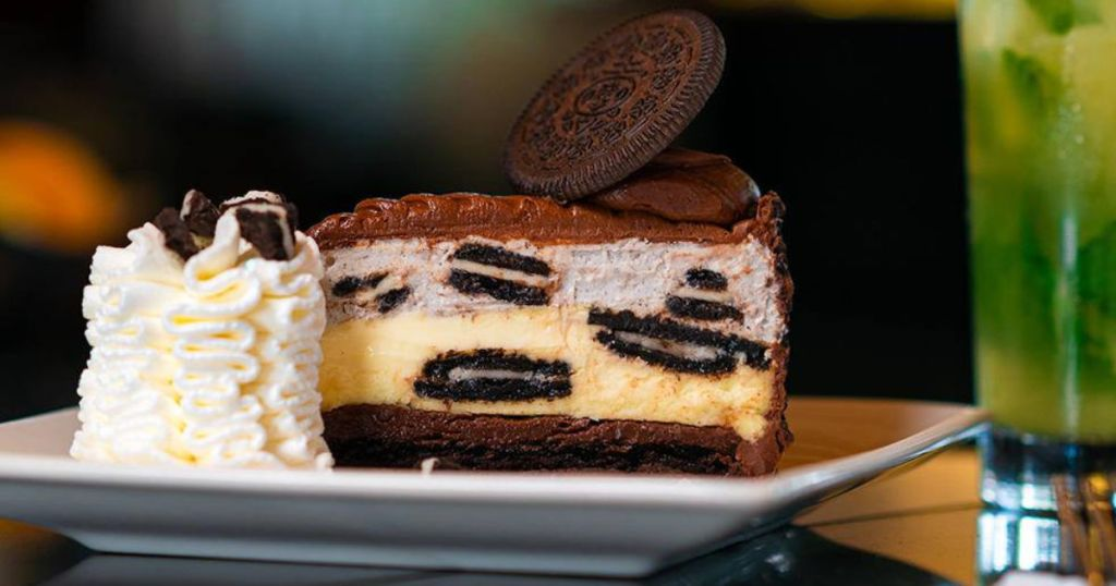 The Cheesecake Factory Oreo Cheesecake on plate with whipped cream and pineapple mojito