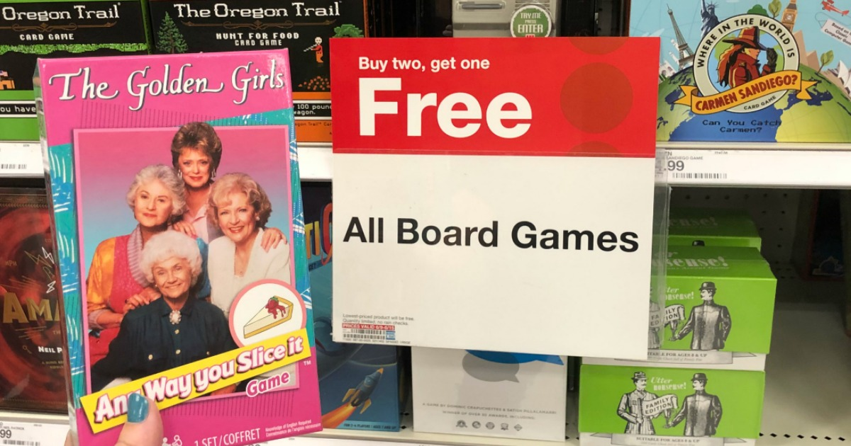 The Golden Girls game is being held by a woman's hand in front of a Target sale sign