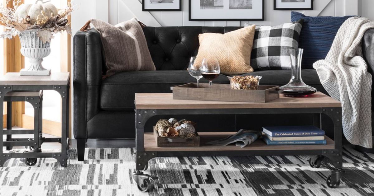 living room scene with a black couch, coffee table, side table, pillows, throws and other decor