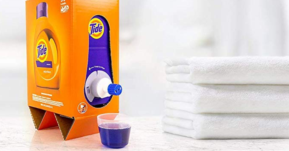 Tide Eco Friendly liquid laundry detergent Box dispensing detergent next to a stack of towels