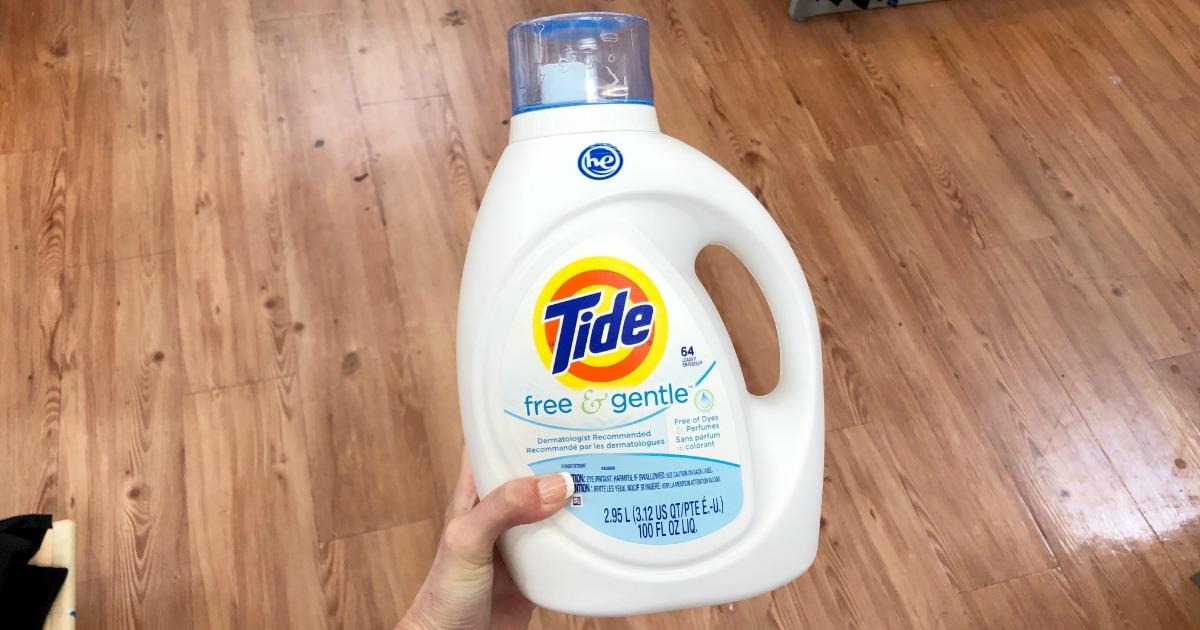 woman's hand holding Tide Free & Gentle detergent bottle above wood floor