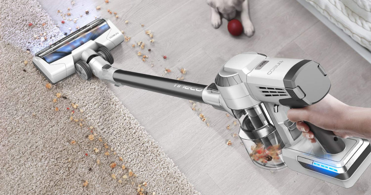 woman vacuuming carpet and tile with puppy next to her