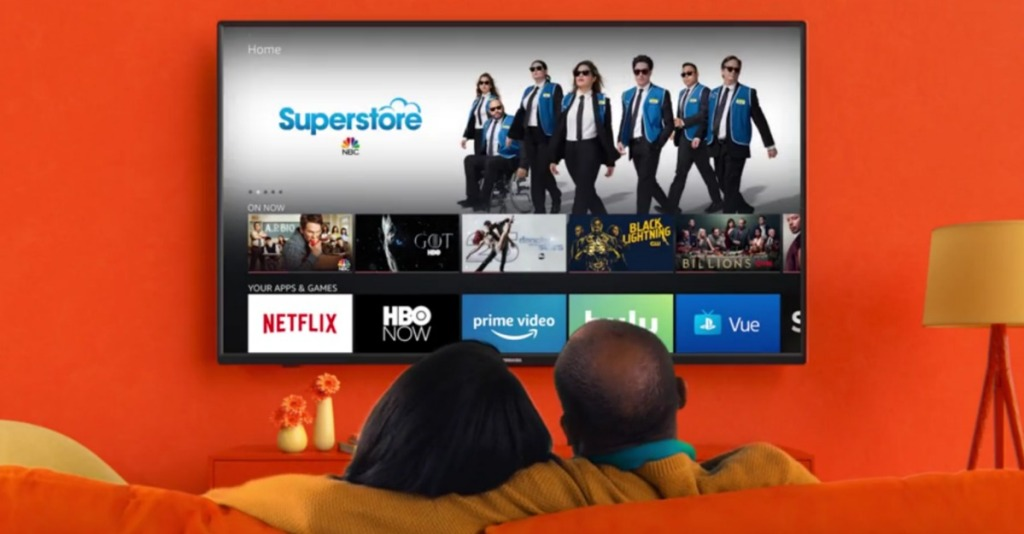 """Toshiba 55"""" TV hanging on orange wall with couple watching from couch"""