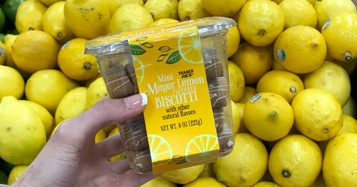 Woman holding container of Trader Joe's Mini Lemon Biscotti in front of lemon display in store
