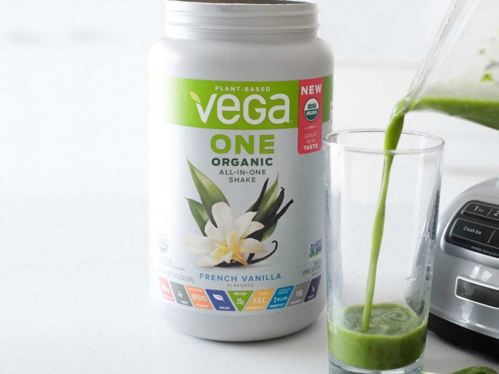 vega one french vanilla protein powder canister sitting on counter by blender pouring a shake into a cup