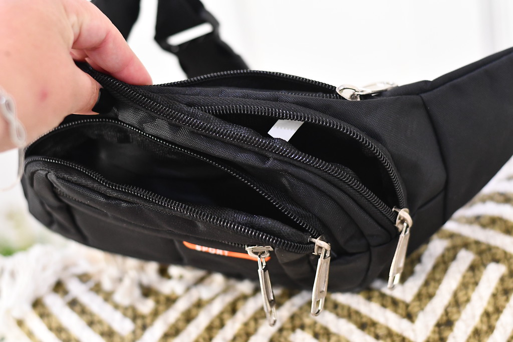 black fanny pack with several pockets being held open