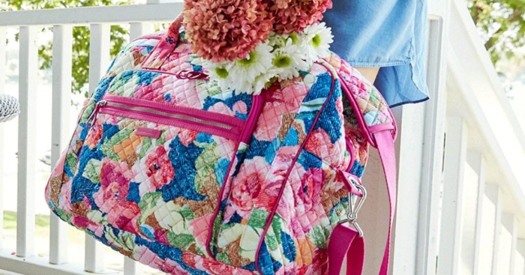 woman holding Vera Bradley weekender bag and flowers