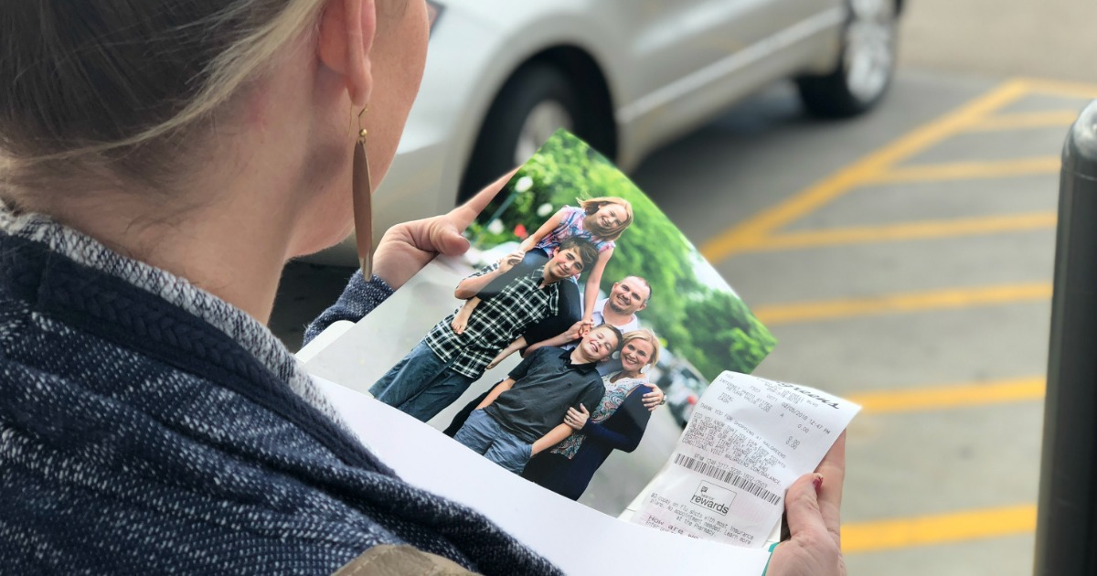 Collin looking at 8x10 photo print featuring her family of 5