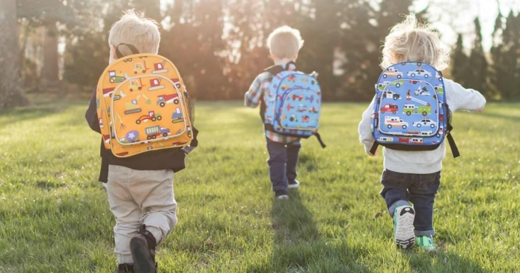 Toddler boys running in field wearing Wildkins Backpacks