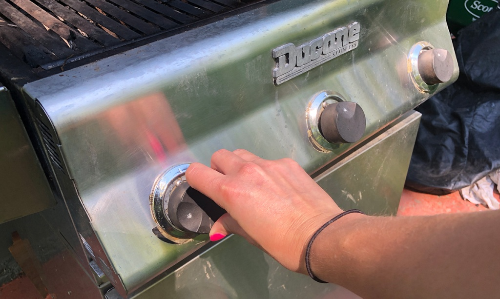 adjusting the dials on a propane grill
