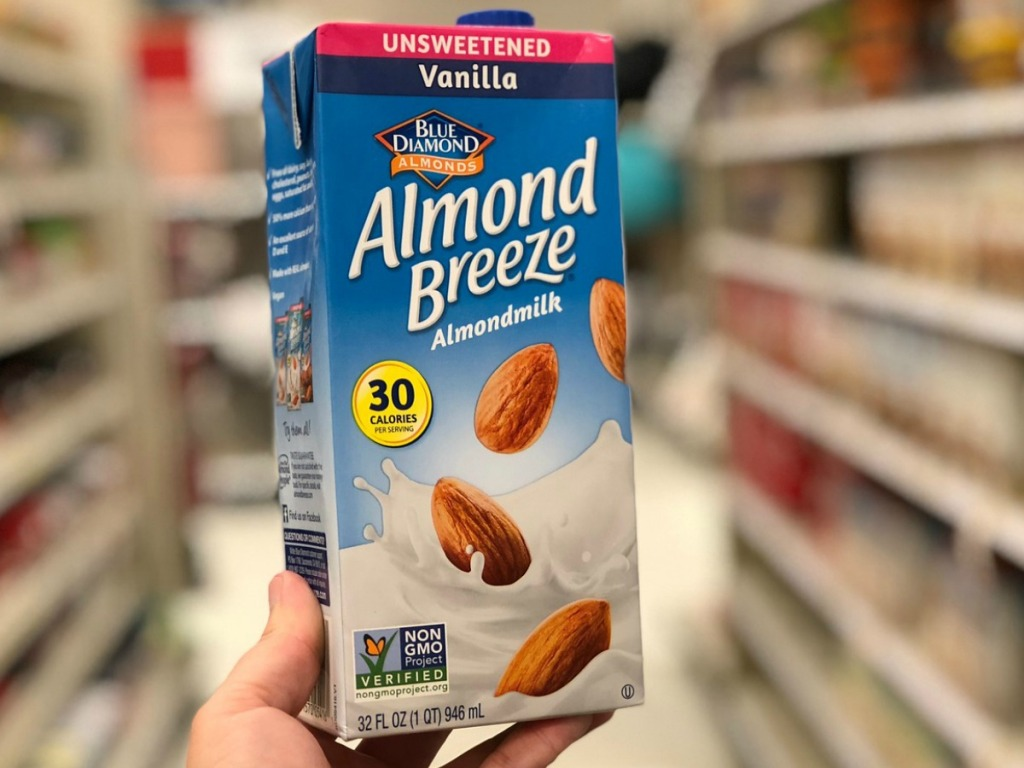 hand holding Almond milk box in store aisle