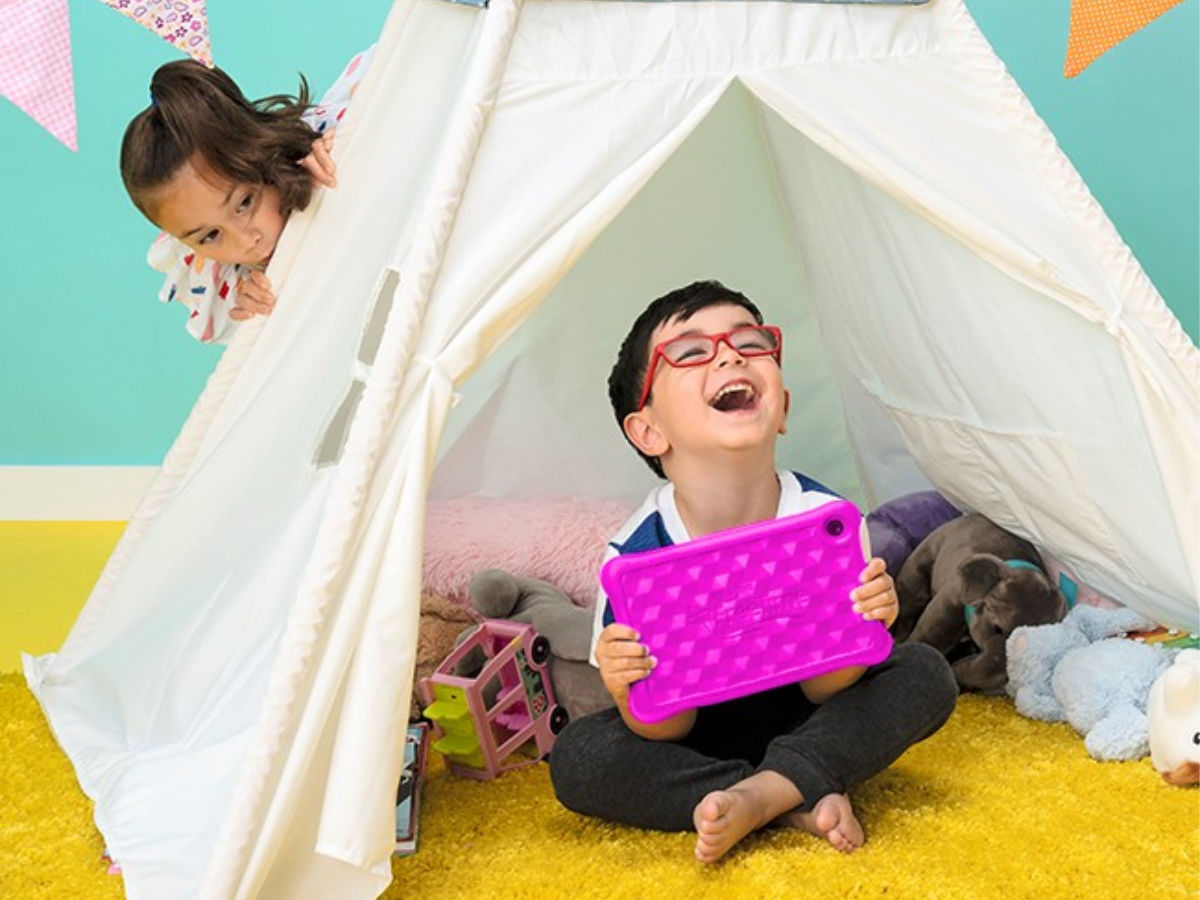 boy holding pink amazon kids fire table sitting in a white tent with girl peaking around the side