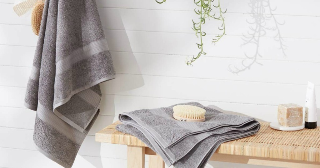amazonbasics gray towel hanging up and folded wash cloth sitting on wicker table