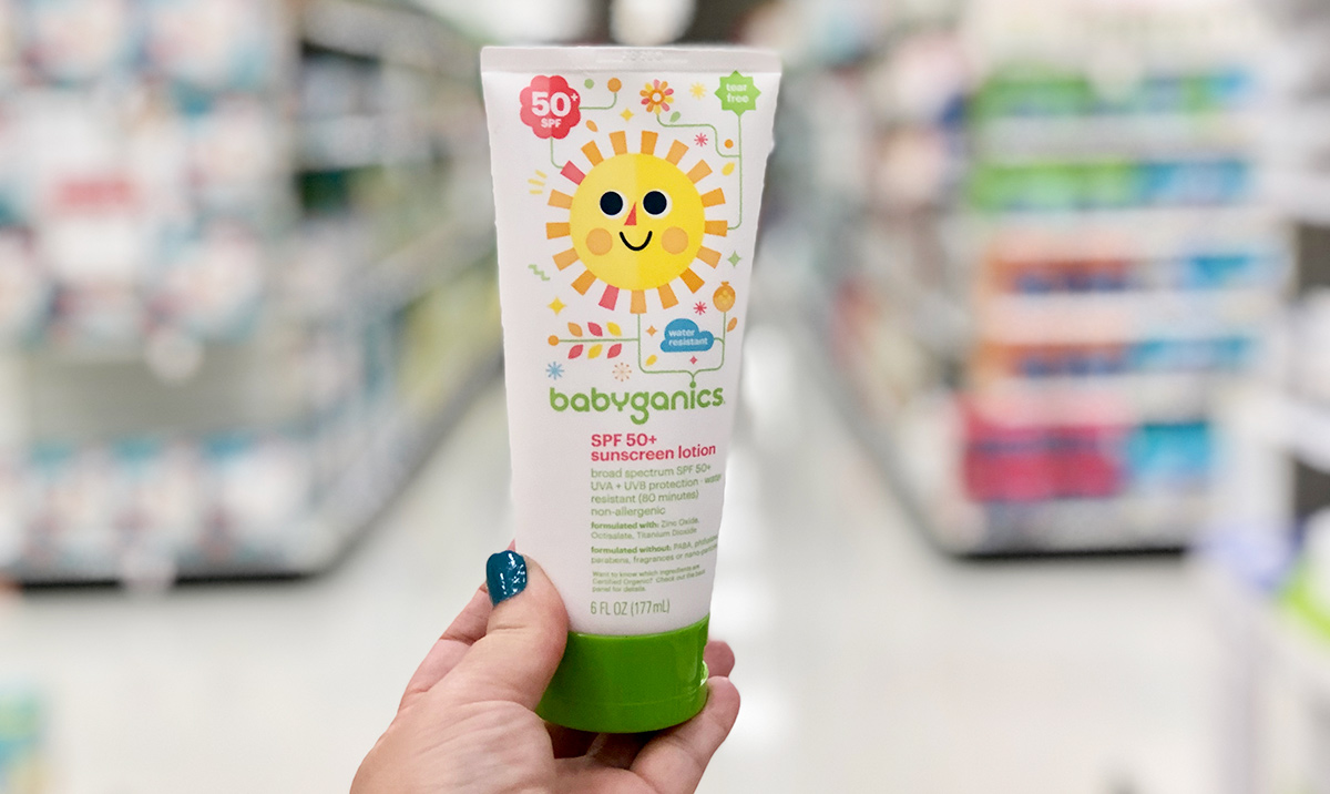 Hand holding a bottle of babyganics sunscreen with store shelves in background