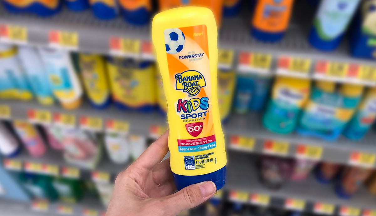 Hand holding a yellow bottle of kids sport banana boat sunscreen with store shelf in background