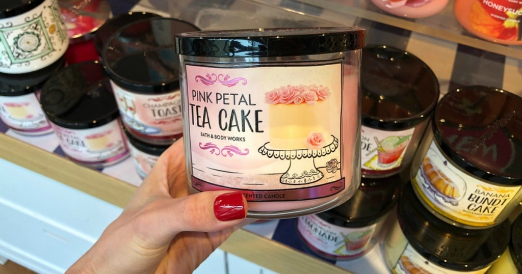 hand holding pink petal tea cake candle with various candles in background