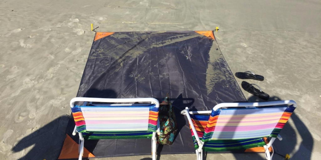 dark gray mat on sand with two beach chairs