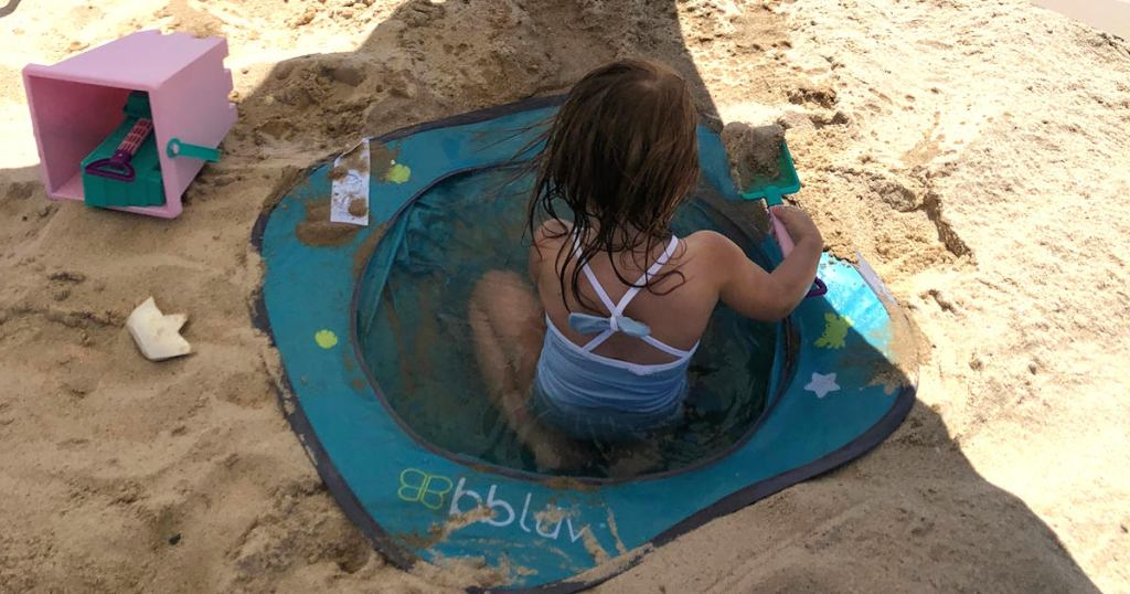 baby girl wearing a blue bathing suit sitting in blue pool in sand
