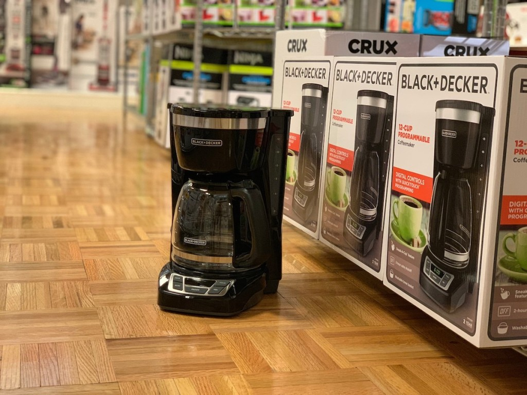 black and decker coffee pot on wood floor in front of product boxes