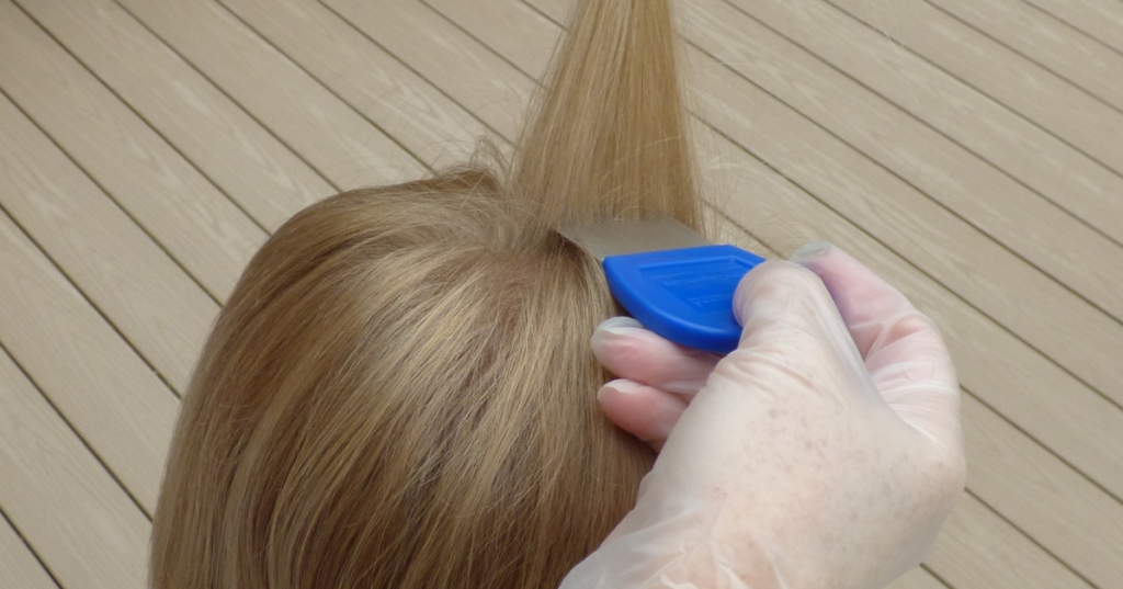 girl with blonde hair and gloved hand holding blue lice comb