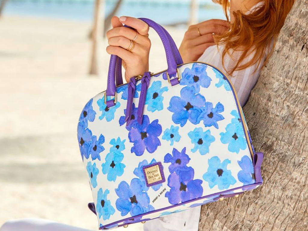 woman holding floral purse on the beach