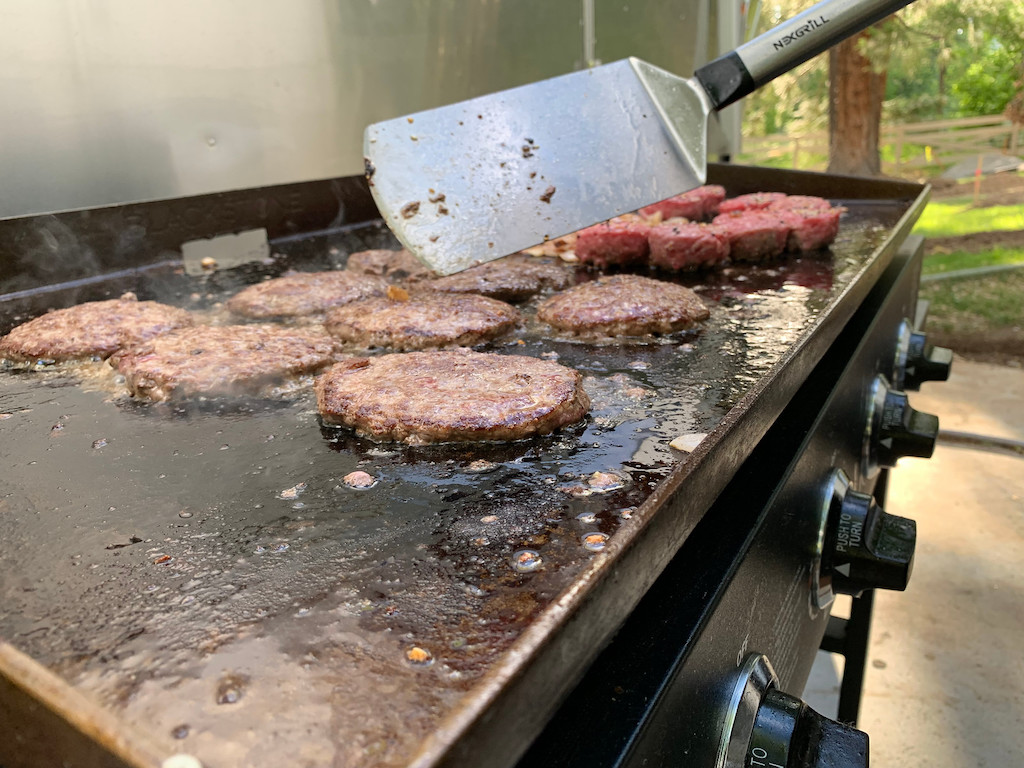 burgers on Blackstone griddle with spatula