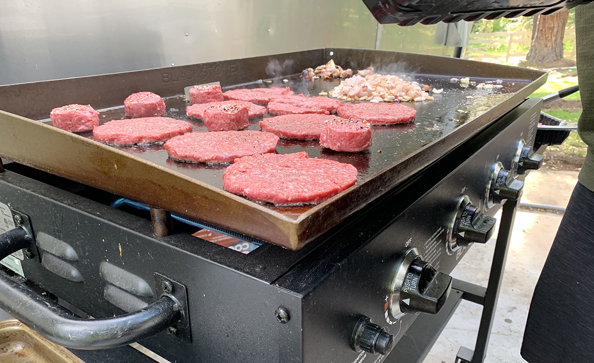 flattened burger patties on griddle cooking surface