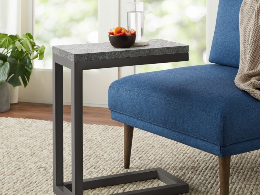 soft chair with small table that has a bowl and cup on it