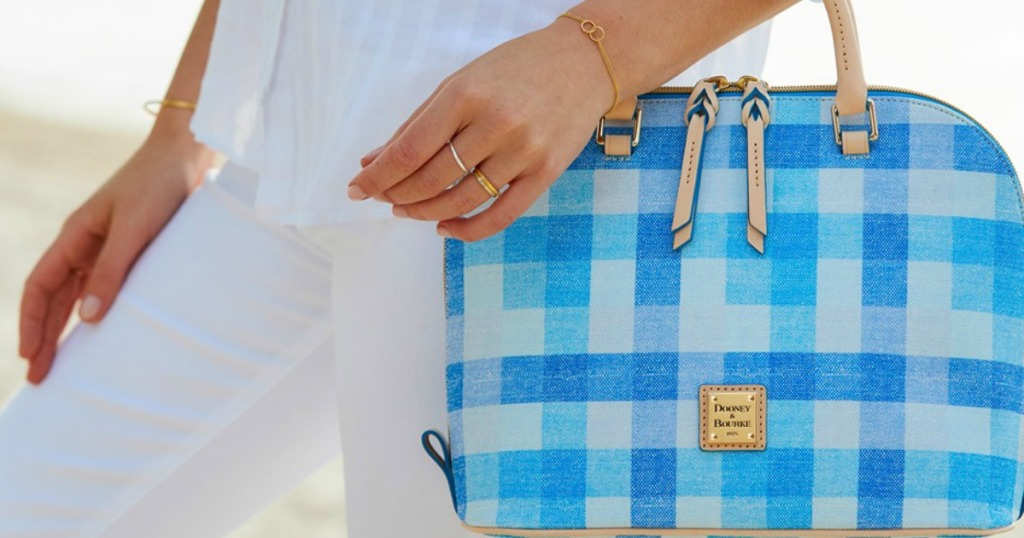 woman holding blue checked purse