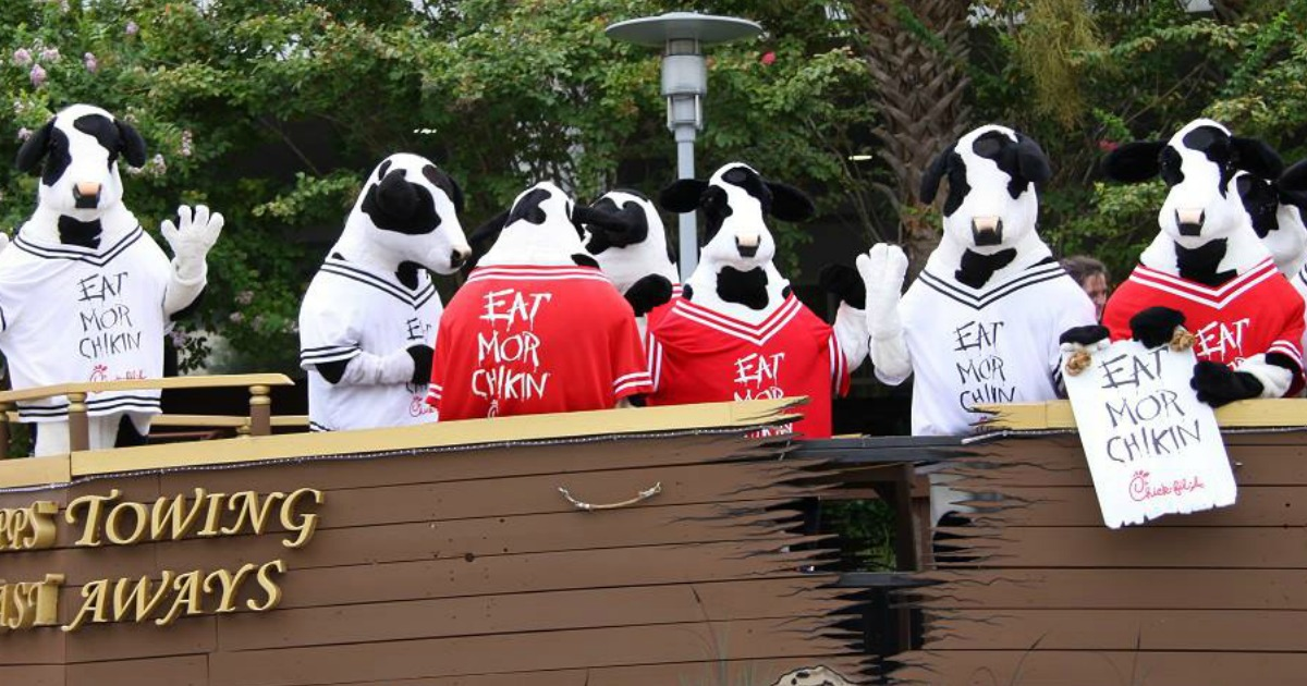 people in cow costumes with eat mor chikin jerseys standing on a parade float